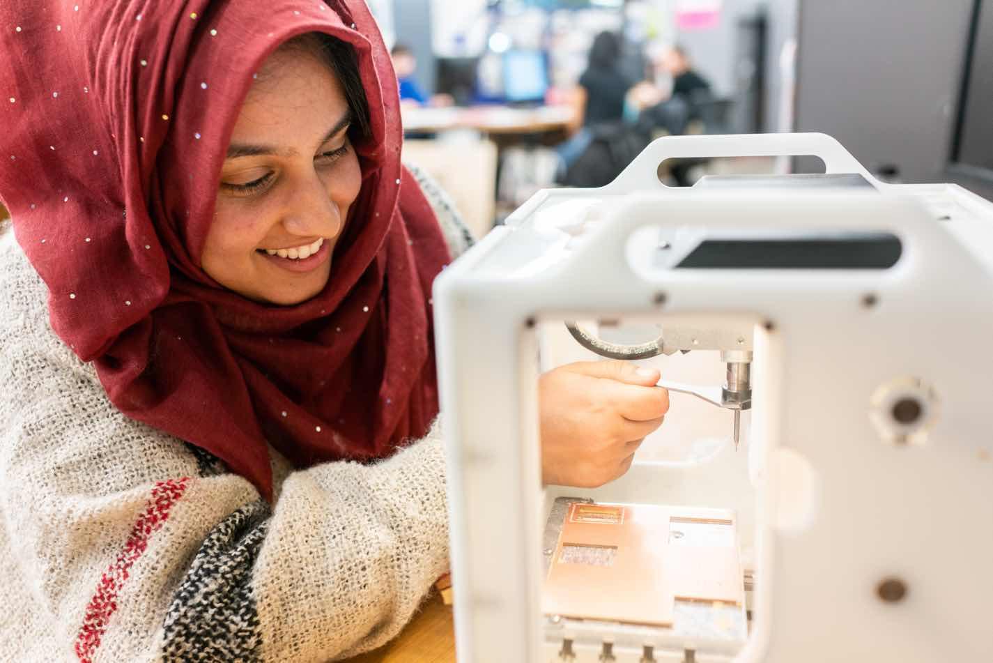 Picture of Masuma Somji at a 3D printer
